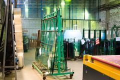 Warehouse at the plant for the production and processing of flat glass. Packs of ready-to-send glass are stored on the Stock Photo