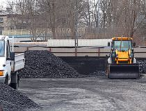 Warehouse for retail sale of coal to the population with a loading excavator of yellow color.Trade in natural resources and minera. Ls.Heating season in houses royalty free stock photography
