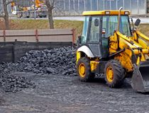 Warehouse for retail sale of coal to the population with a loading excavator of yellow color.Trade in natural resources and minera. Ls.Heating season in houses stock image
