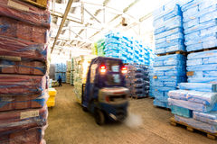 Warehouse with riding forklift and stacks of box at factory. Warehouse with riding forklift and stacks of packed boxes at factory Royalty Free Stock Image