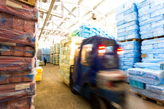 Warehouse with riding forklift and stacks of box at factory. Warehouse with riding forklift and stacks of packed boxes at factory close up Stock Image