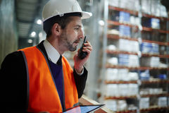 Warehouse Supervisor Managing Work Operations. Side view portrait of warehouse supervisor speaking by walkie-talkie while looking down from balcony at tall racks royalty free stock images
