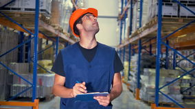 A warehouse supervisor takes notes on his clipboard. stock footage