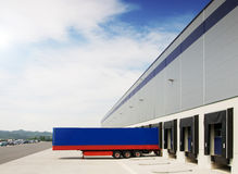 Warehouse. Blue transport truck during import (export) supply stocks in a large warehouse Royalty Free Stock Image