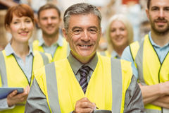 Warehouse team with arms crossed wearing yellow vest Stock Photo