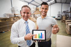 Warehouse team showing column graphic to the camera Royalty Free Stock Photography