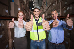 Warehouse team smiling at camera showing thumbs up Stock Images