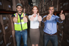 Warehouse team smiling at camera showing thumbs up Royalty Free Stock Photo