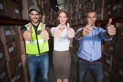 Warehouse team smiling at camera showing thumbs up Royalty Free Stock Photo