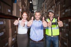 Warehouse team smiling at camera showing thumbs up Royalty Free Stock Photos