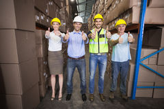Warehouse team smiling at camera showing thumbs up Stock Photos