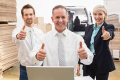 Warehouse team smiling at camera showing thumbs up Royalty Free Stock Image