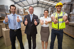 Warehouse team smiling at camera showing thumbs up Stock Image