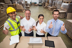 Warehouse team smiling at camera showing thumbs up Royalty Free Stock Image