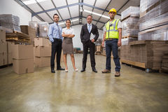 Warehouse team standing looking at camera. In a large warehouse Stock Photos
