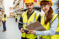 Warehouse team working together with clipboard. In a large warehouse Stock Photos