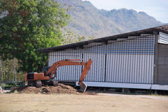 A warehouse under construction in the middle of the mountain with back hoe parks next to it. Royalty Free Stock Photo