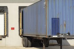 Warehouse unloading. Blue trailor parked at the loading bay at a warehouse Royalty Free Stock Photo