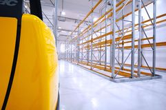 Warehouse view with forklift truck portion on the left. Warehouse view with yellow forklift truck portion on the left Stock Photos