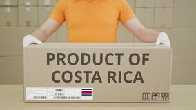 Warehouse Worker And Big Box With PRODUCT OF COSTA RICA Printed Text Stock Photo