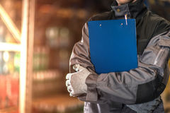 Warehouse worker with blue clipboard closeup photo. stock photography