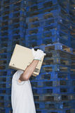Warehouse Worker Carrying Box. Side view of a warehouse worker carrying box in front of stacks of pallets Royalty Free Stock Photos