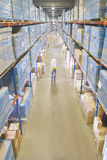 Warehouse worker carrying boxes in aisle Royalty Free Stock Image