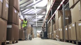 Warehouse worker carrying cardboard boxes stock video