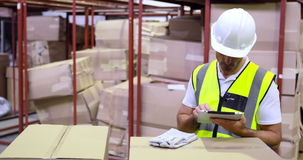 Warehouse worker checking boxes for shipping with tablet pc Royalty Free Stock Photos