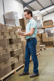 Warehouse worker checking his list on clipboard Stock Photography