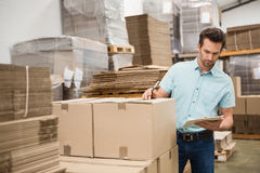 Warehouse worker checking his list on clipboard Royalty Free Stock Images