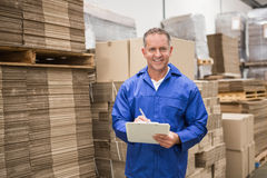 Warehouse worker checking his list on clipboard. In a large warehouse Stock Image