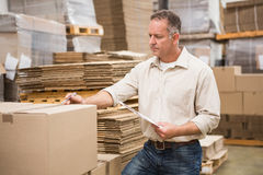 Warehouse worker checking his list on clipboard. In a large warehouse Royalty Free Stock Photos