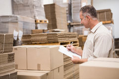 Warehouse worker checking his list on clipboard Stock Images