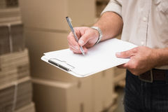 Warehouse worker checking his list on clipboard. In a large warehouse Royalty Free Stock Photography