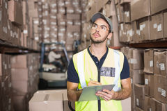 Warehouse worker checking his list. In a large warehouse Stock Photos
