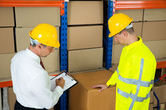 Warehouse Worker Checking The Inventory With Manager Royalty Free Stock Image