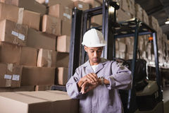 Warehouse worker checking time. In the warehouse Stock Photography