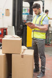 Warehouse worker with clipboard. In warehouse Stock Photos