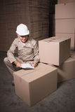 Warehouse worker with clipboard. In warehouse Royalty Free Stock Photography