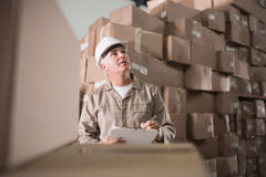 Warehouse worker with clipboard. In warehouse Royalty Free Stock Images