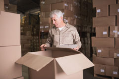 Warehouse worker with clipboard. In warehouse Stock Image