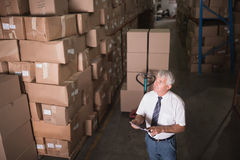 Warehouse worker with clipboard. In warehouse Stock Images