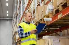 Warehouse worker with clipboard and plastic box. Logistic business, shipment and people concept - male worker with clipboard and plastic box in reflective safety Royalty Free Stock Image
