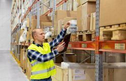 Warehouse worker with clipboard and plastic box. Logistic business, shipment and people concept - male worker with clipboard and plastic box in reflective safety Stock Images