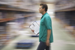 Warehouse Worker With Clipboard. Side view of a warehouse worker walking with a clipboard Royalty Free Stock Photos