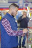 Warehouse worker with clipboard in warehouse. Clipboard Stock Photography
