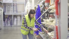 Warehouse worker conducts accounting with barcode scanner. Girl warehouse worker in protective clothing holds inventory with barcode scanner stock footage