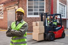 Warehouse worker with crossed arms in front of a forklift stock image