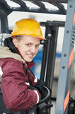 Warehouse worker driver in. Young smiley warehouse worker driver in uniform driving forklift stacker Stock Image